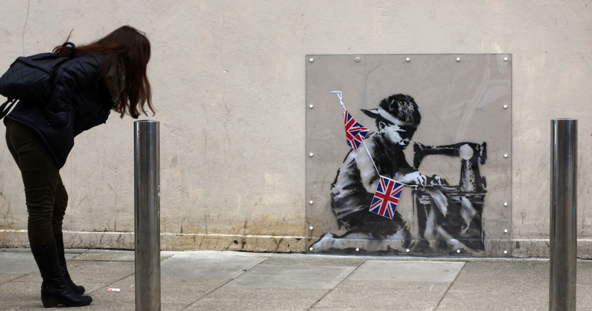 A woman looks at an artwork attributed to Banksy under a plastic cover on May 17, 2012 in London, England. The stenciled image depicts a poor child making Union Jack flags on a sewing machine and is located on the wall of a Poundland discount shop in the Wood Green area of north London.</p>