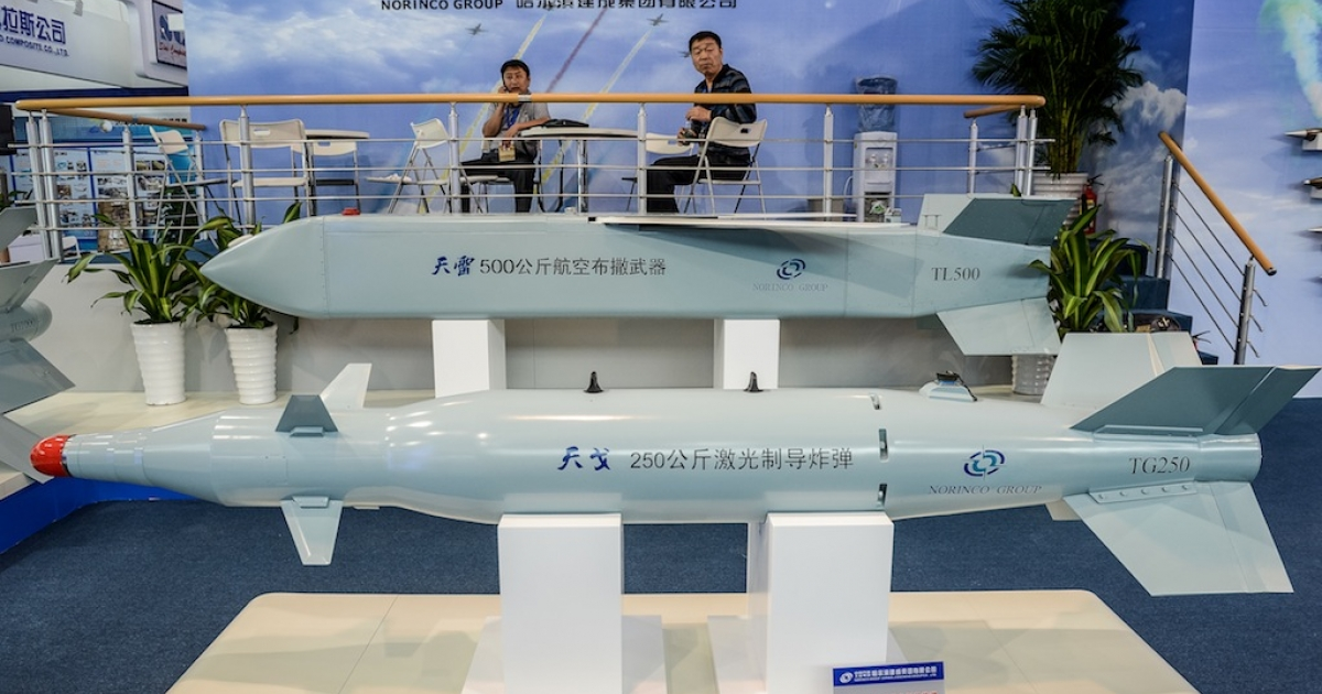 Men sit by a display of missiles models from Chinese manufacturer Norinco Group on the eve of the ninth China International Aviation and Aerospace Exhibition in Zhuhai on Nov. 12, 2012.</p>