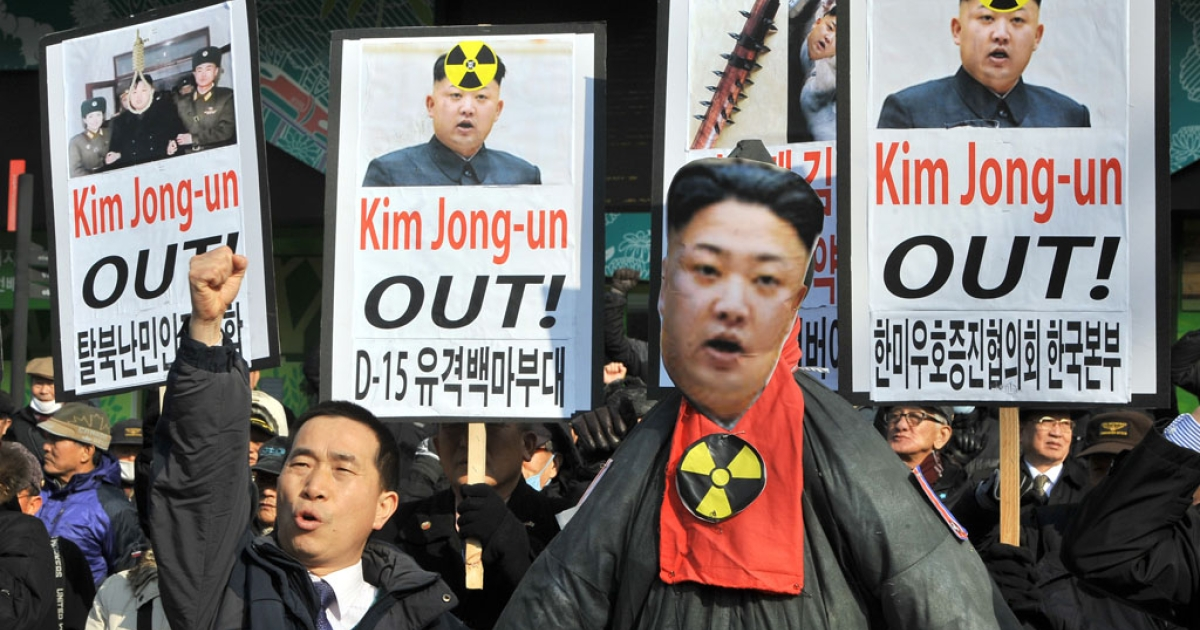 South Korean activists shout slogans behind an effigy of North Korean leader Kim Jong-Un during a rally denouncing North Korea's nuclear test, in Seoul on February 13, 2013.</p>