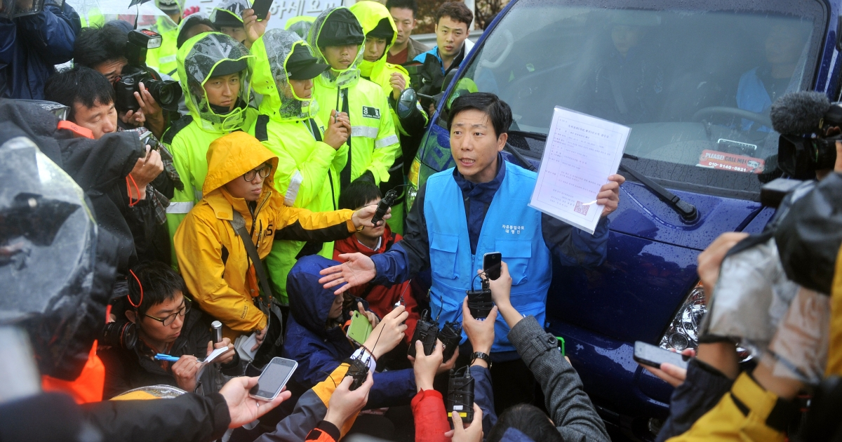 Park Sang-Hak (C), an activist and former defector from North Korea, complains with a state document approving his planned rally near the border as policemen block his truck containing anti-North Korea leaflets on a roadway in Paju, north of Seoul, on October 22, 2012.</p>