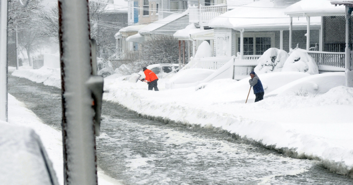 People shovel snow as flood waters go down Coral Street on Feb. 9, 2013, in Winthrop, Massachusetts. An overnight blizzard left one to three feet of snow in areas, and coastal flooding is expected as the storm lingers into the day.</p>