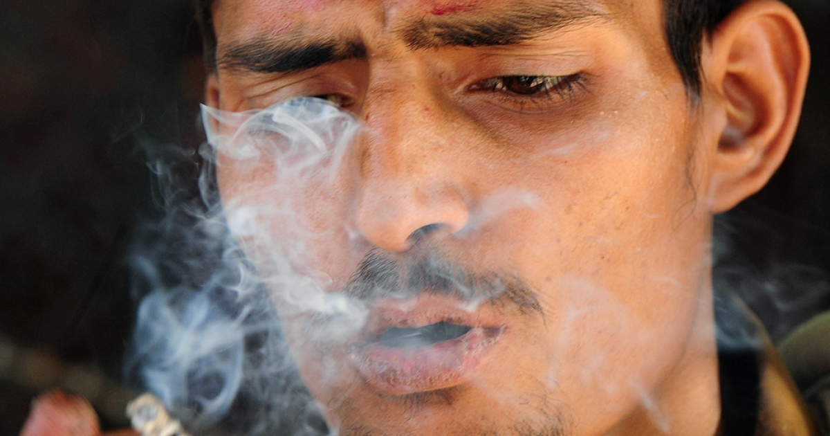 This photograph taken on May 31, 2012, shows a Pakistani drug addict smoking hashish in the northwestern city of Peshawar. This may be conservative Muslim country, where women are confined to their homes and alcohol banned, but marijuana and hashish are much loved indulgences.</p>
