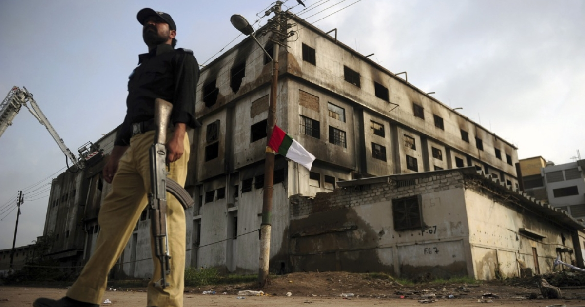 A Pakistani policeman stands guard outside a burnt-out garment factory in Karachi, Pakistan.</p>