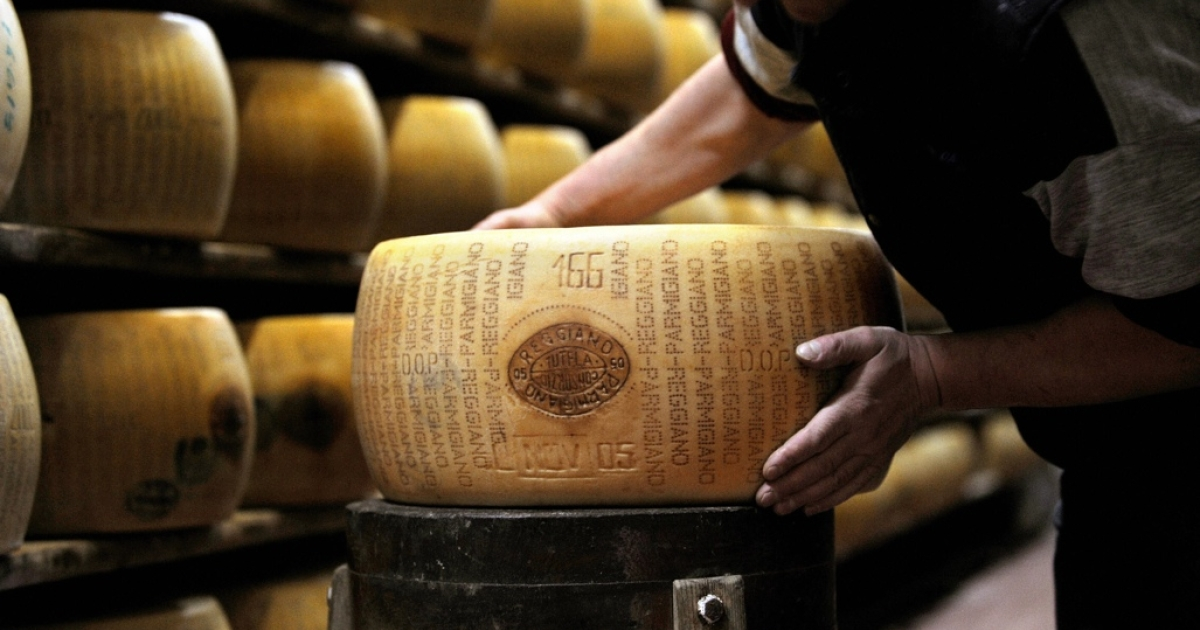 A worker checking a wheel of seasoned Parmigiano Reggiano cheese in a factory in Valestra.</p>