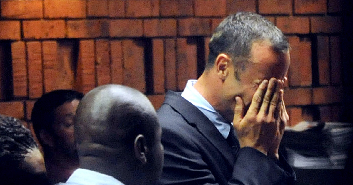 Olympic sprinter Oscar Pistorius (R) hides his face in his hands in the court room during his hearing on charge of murdering his model girlfriend Reeva Steenkamp on Valentine's Day on February 15, 2013 at the Magistrate Court in Pretoria.</p>