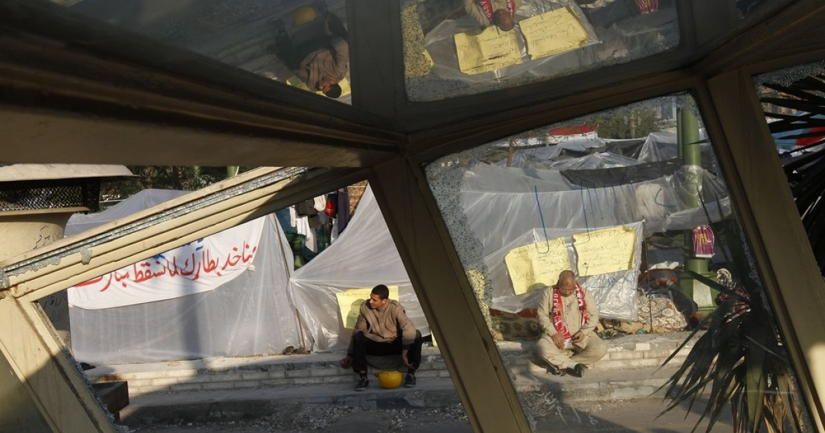 Anti-government protesters sit in front of their plastic sheeting tents early morning in Tahrir Square on February 8, 2011, on the 15th day of protests calling for an end to President Hosni Mubarak's regime.</p>