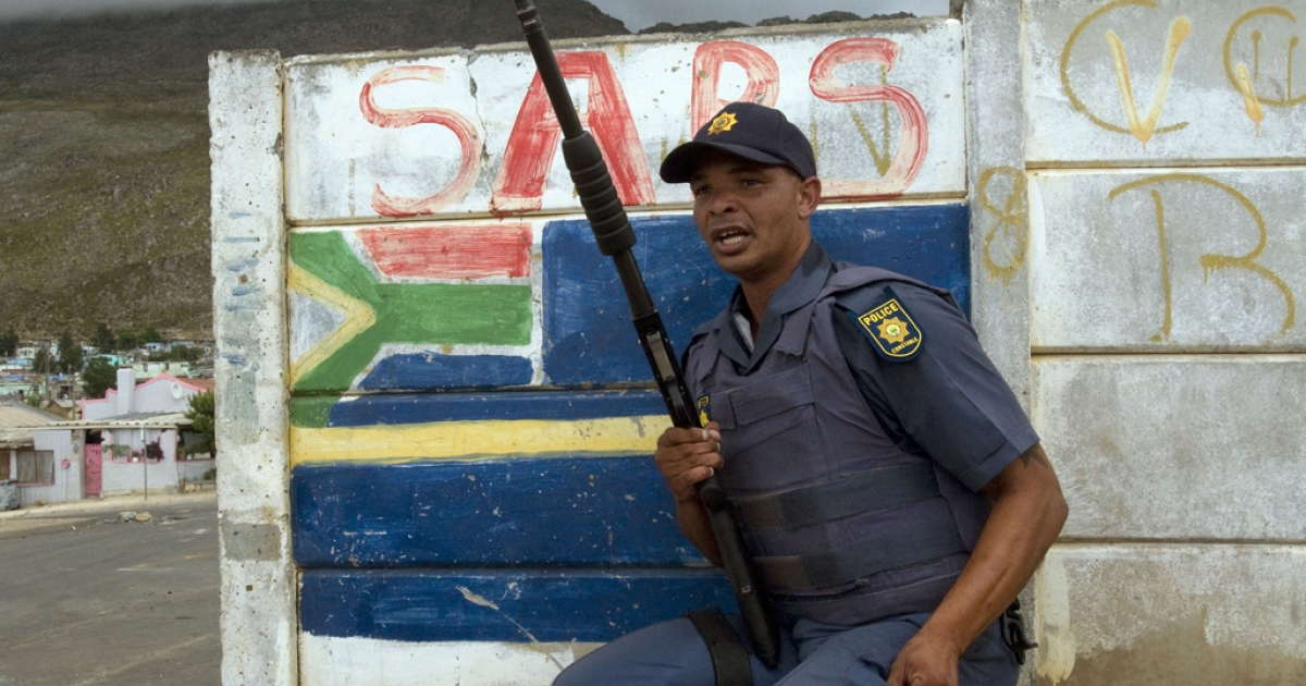 A member of the South African Police Services (SAPS) takes cover behind a wall from rocks being thrown by protesters during a farm worker strike on January 14, 2012 in Villiersdorp, a small farming town about 100 km borth of Cape Town, South Africa.</p>