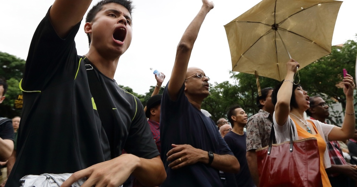 People react to a speaker speech at Hong Lim Park during the protest against the government's White Paper on Population at Speakers' Corner on February 16, 2013 in Singapore.</p>