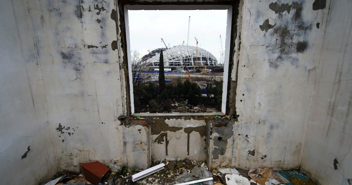 The central stadium for the Winter Olympics 2014 is seen through the window of a derelict house in Sochi on Feb. 18, 2013.</p>