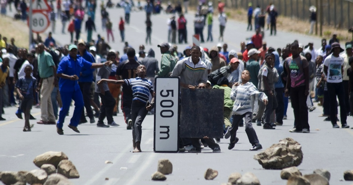 Striking farm workers and other protestors throw stones, while hiding behind broken road signs during violent clashes with members of the South African Police Services (not visible), on January 10, 2013 in de Doorns, a small farming town about 140 km North of Cape Town, South Africa. The farm workers have said that they they will not return to work on the fruit growing region's farms until they receive a daily wage of at least R150 ($17) per day, which is about double what they currently earn.</p>