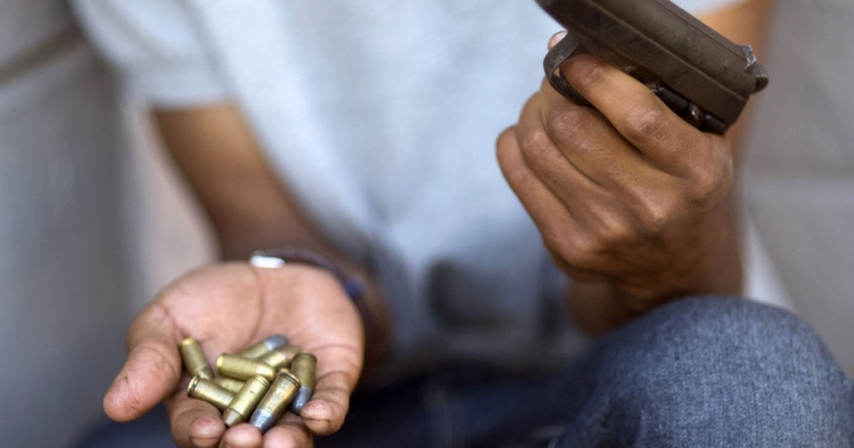 A young gang member shows a gun and ammunition in in Cape Town, South Africa.</p>