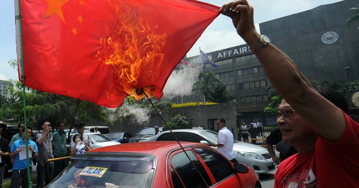 A Filipino activist burns a Chinese flag during a protest in Manila on July 27, 2012, amidst the heightening tension between the Philippines and China over the disputed South China Sea.</p>