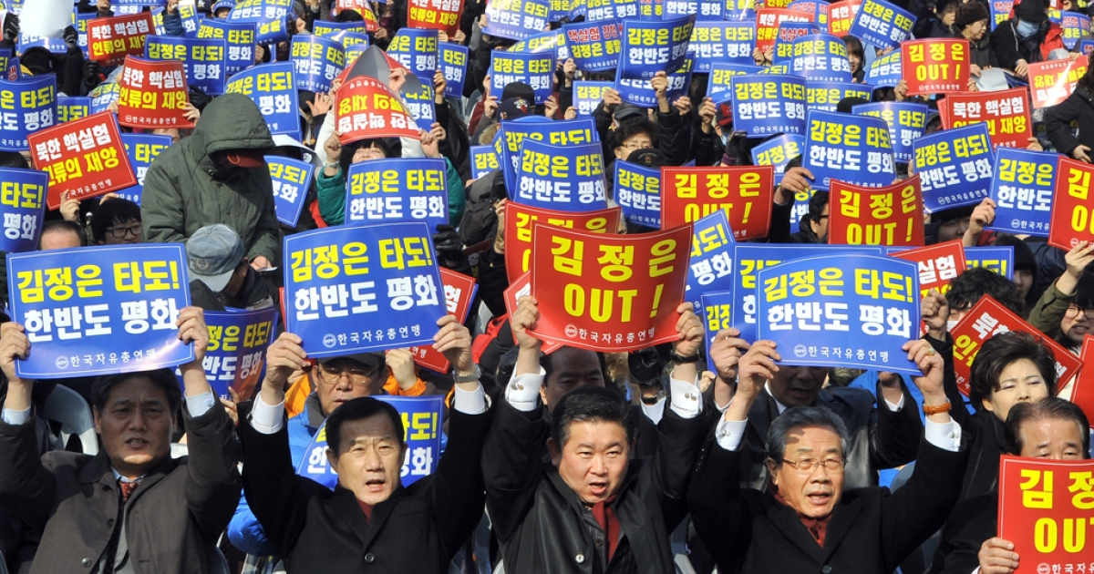 South Korean protestors hold up banners reading