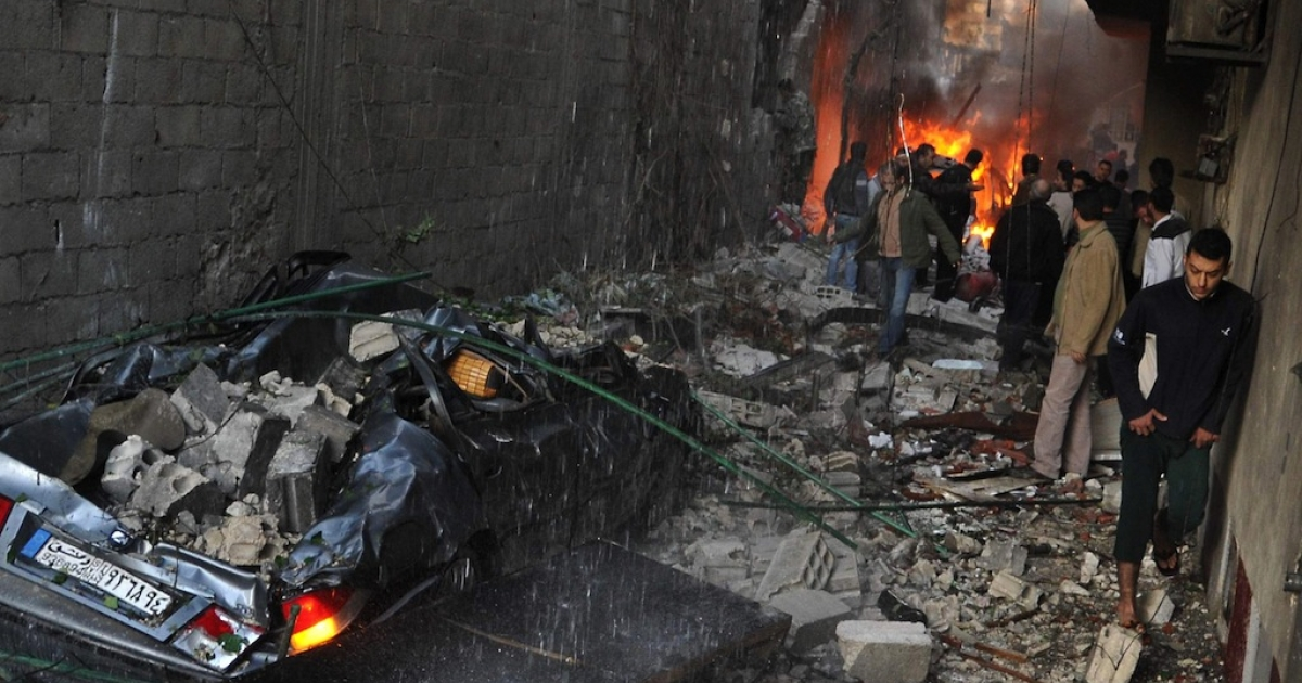 Syrian men inspect the scene of a car bomb explosion in Jaramana, a mainly Christian and Druze suburb of Damascus, on Nov. 28, 2012.</p>