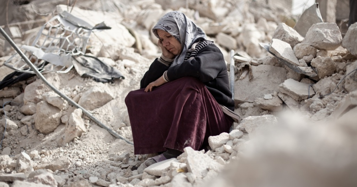 Syrian Zakia Abdullah sits on the rubble of her house in the Tariq al-Bab district of the northern city of Aleppo on Feb. 23, 2013.</p>