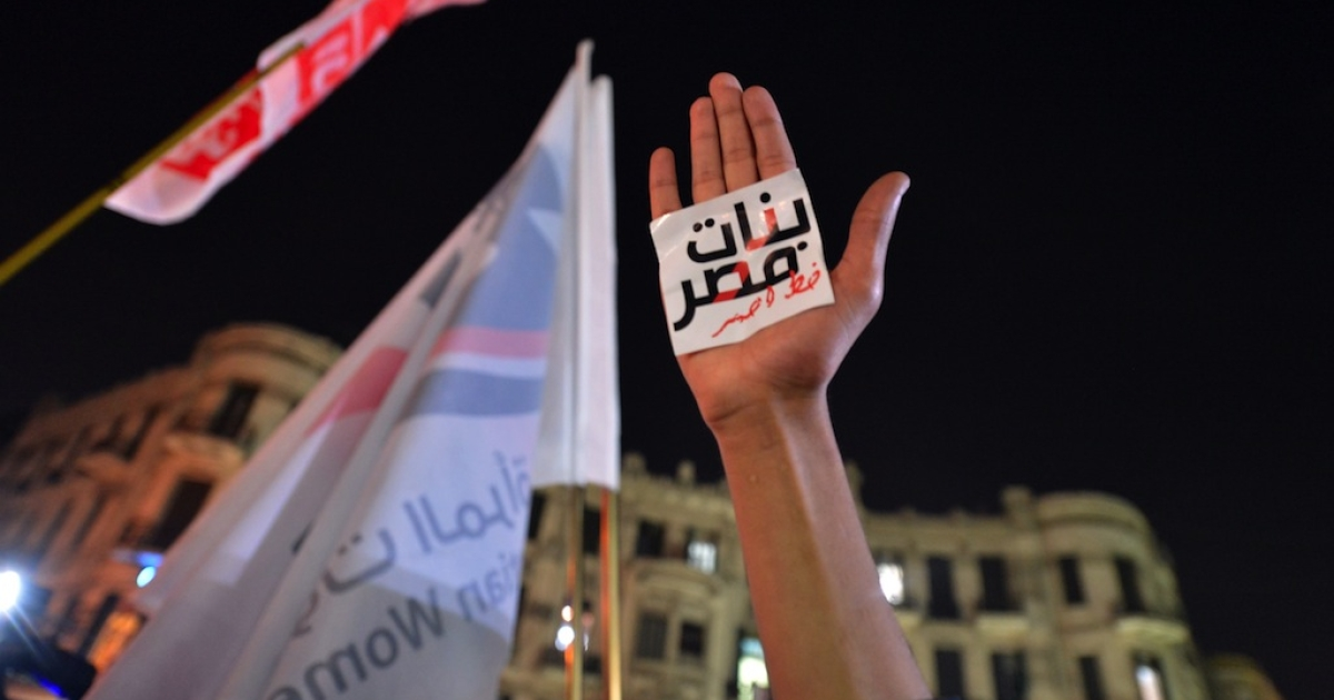 An Egyptian protester hold up his hand with a slogan reading in Arabic: