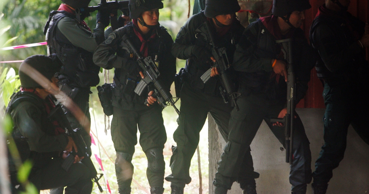 Thai police stand guard during a suspected insurgents attack at a military base in Thailand's restive southern province of Narathiwat on February, 13, 2013.  The Thai government agreed on February 28, 2013 to peace talks with Muslim rebels operating in the south.</p>