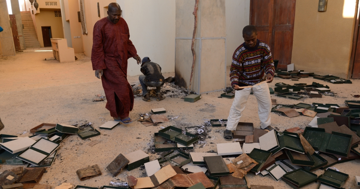 Men recover burnt manuscripts at the Ahmed Baba Center for Documentation and Research in Timbuktu, Mali, on Jan. 29, 2013. As French-led forces recaptured Mali's desert city of Timbuktu, fleeing Islamists set fire to a building that housed priceless ancient manuscripts.</p>