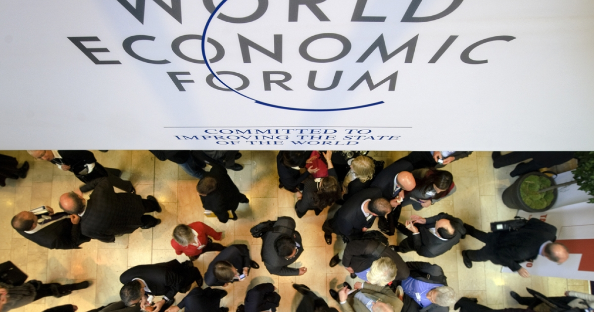 Participants at the World Economic Forum (WEF) chat under a sign on Jan. 25, 2012, at the Congress Center in the Swiss municipality of Davos. The world's political and business elites met with some 40 heads of government for five days to discuss all things related to the global economy.</p>