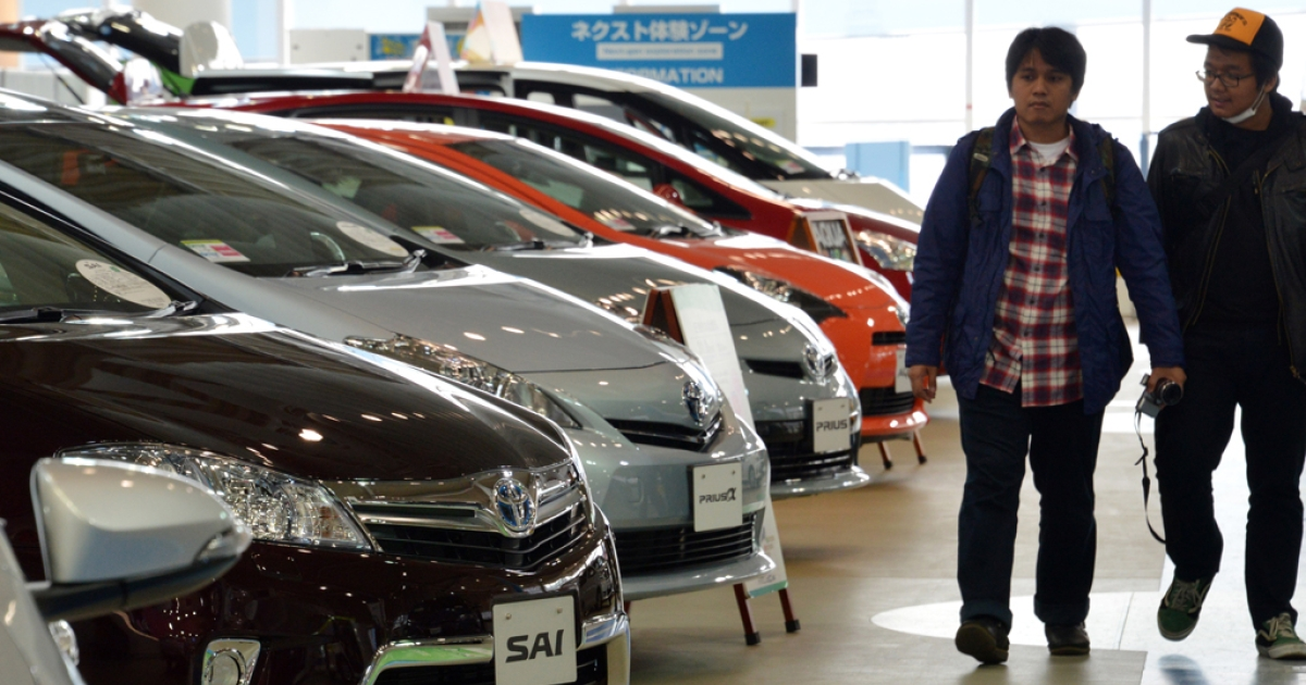 People look at Toyota Motor vehicles at the company's showroom in Tokyo, Japan, on Feb. 5, 2013. Toyota recently raised its annual net profit forecast by more than 10 percent on strong sales of the Camry sedan and other vehicles in the US.</p>
