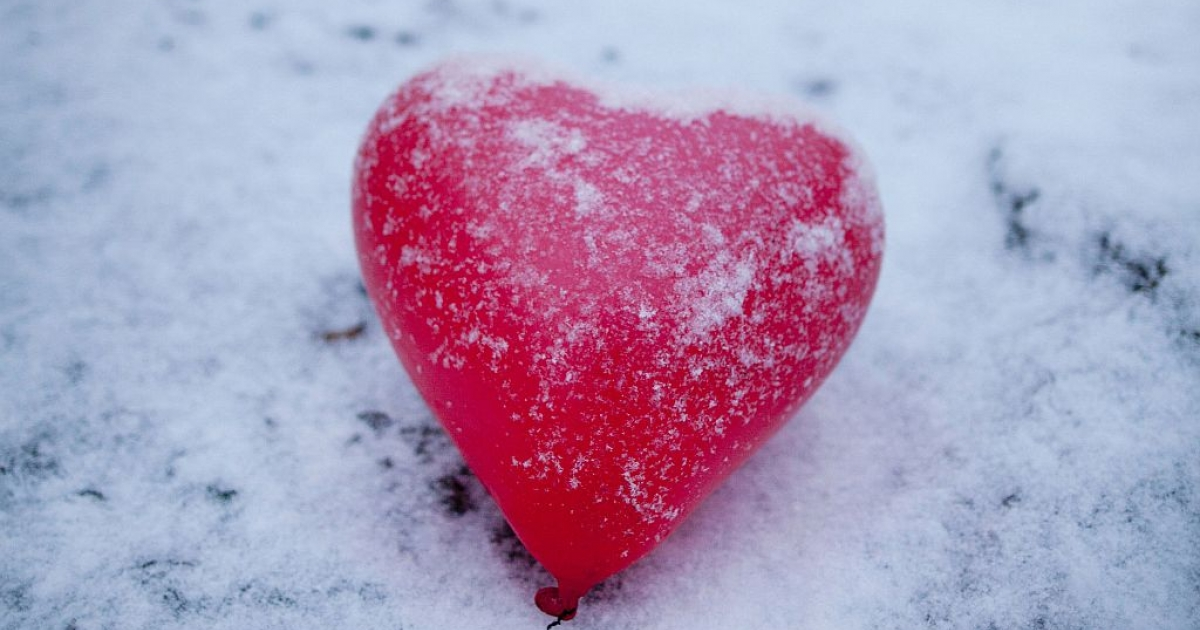 A red heart-shaped balloon lays in the snow.</p>