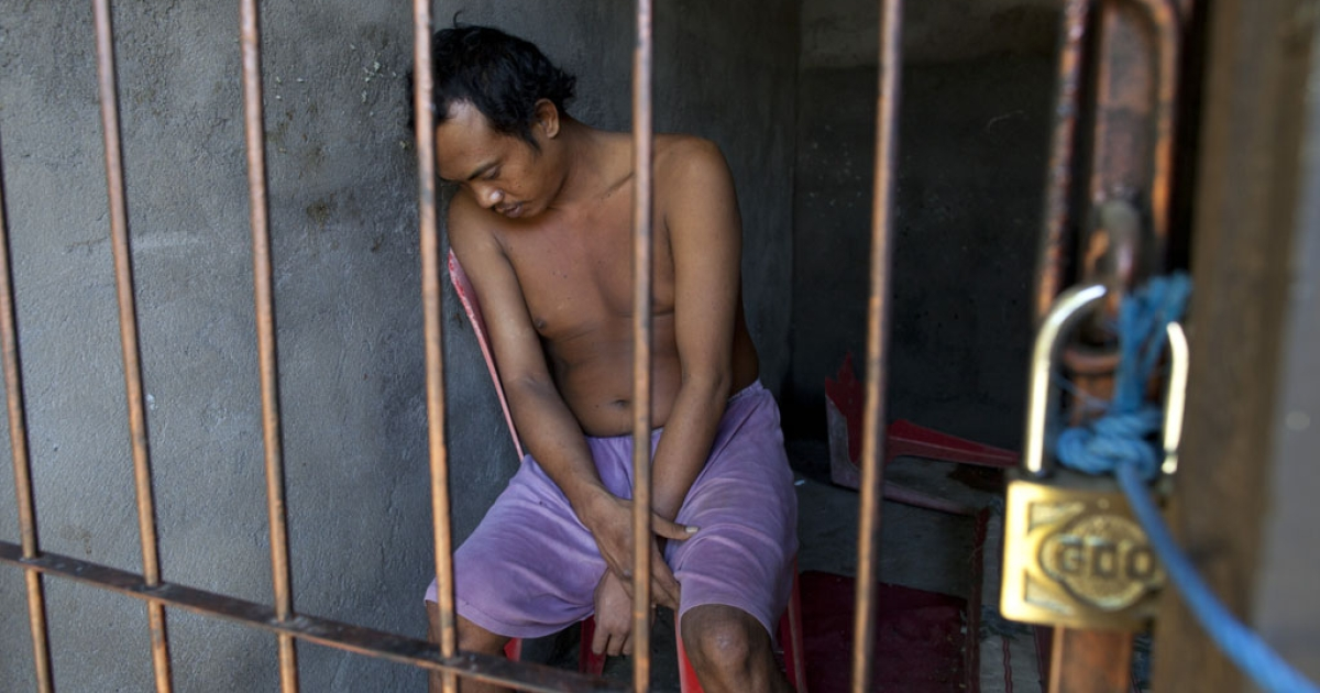 Gede, 35, sits in his cell May 5, 2012 in Buleleng, Bali, Indonesia. His family keeps him in a locked room to control him so he doesn't run away and disturb the community. Diagnosed with Schizophrenia, he has had mental problems since 2001 and has been hospitalized seven times. The Indonesian health ministry spends 2.3 percent of the total national budget on health care for a population of approximately 240 million people. Bali has a shortage of psychiatrists and one government-run mental hospital.</p>