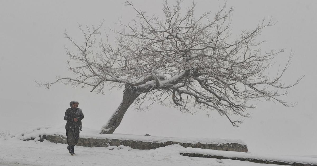An Afghan man walks as snow falls in Kabul.</p>