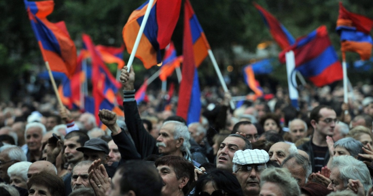 Armenian opposition supporters hold national flags during a rally in Yerevan on September 30, 2011.</p>