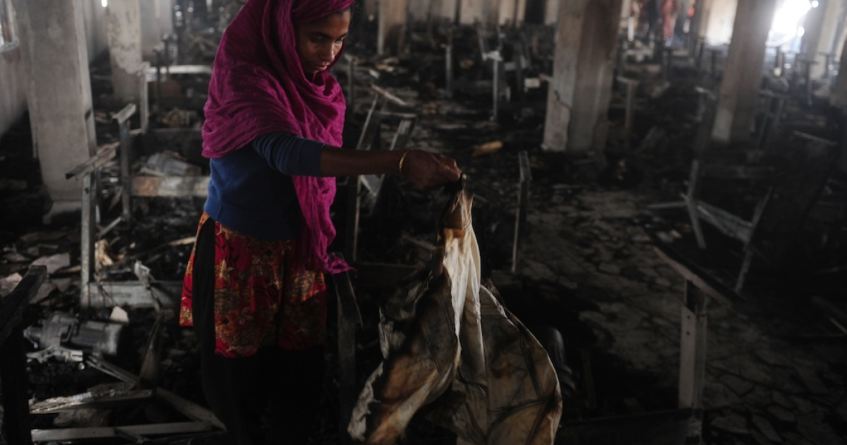 Factory worker Bangladeshi Shahinur looks though the devastation after a fire swept though the garment factory in Dhaka on January 27, 2013. At least seven female workers were killed after a blaze swept through a small garment factory in the Bangladeshi capital, police and fire officials said.</p>
