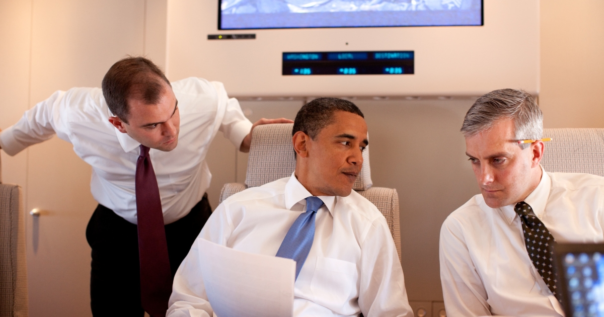 Denis McDonough (R, with pencil behind ear) conferring with President Barack Obama and speechwriter Ben Rhodes on Air Force One en route to Cairo, Egypt, on June 4, 2009.</p>