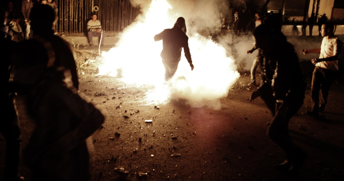 An Egyptian protester kicks a live tear gas canister into a fire during clashes with riot police near Tahrir Square on Jan. 27, 2013, in Cairo, Egypt. Violent protests continued across Egypt two days after the second anniversary of the Egyptian Revolution that overthrew former President Hosni Mubarak.</p>