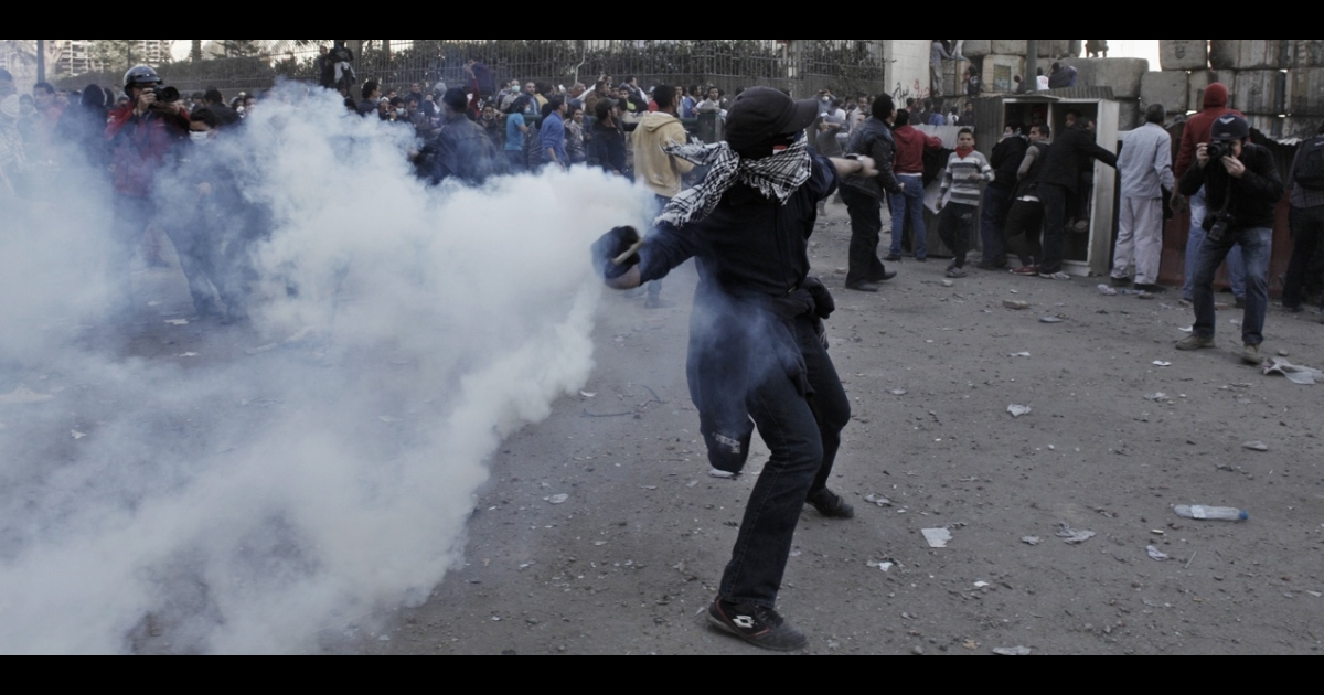 An Egyptian protester throws a live tear gas canister back toward riot police in Tahrir Square on Jan. 25, in Cairo, Egypt.</p>