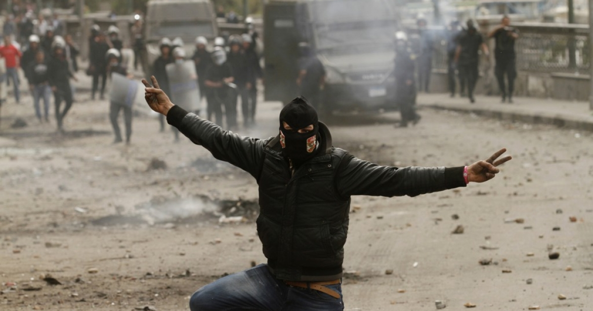 An Egyptian protester flashes the sign for victory during clashes with riot police near Cairo's Tahrir Square on Jan. 28, 2013.</p>