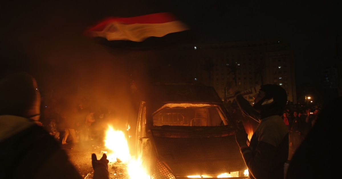 An protester waves the Egyptian flag near a police vehicle on fire in Cairo's Tahrir Square on Jan. 28, 2013.</p>