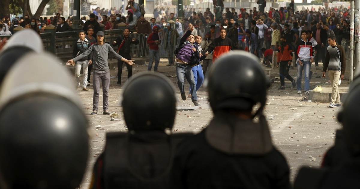 Egyptian protesters throw stones towards riot policemen during clashes near Cairo's Tahrir Square on January 27, 2013. Clashes killed at least 31 people in Egypt's Port Said as violence raged in several cities including the capital following death sentences passed on 21 football fans after a riot.</p>