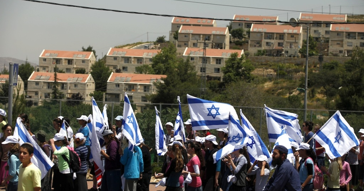 Israeli settlers wave their national flag as they march from the Ulpana outpost to the High Court of Justice in Jerusalem, on June 4, 2012 in Beit El, West Bank.</p>