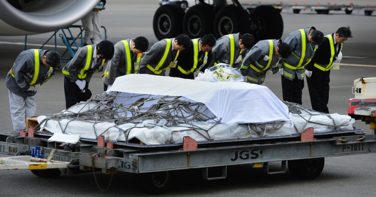 Ground staff members bow after a coffin carrying the last Japanese victim of the Algerian hostage crisis was unloaded from a plane at Narita Airport, outside Tokyo on January 26, 2013. The body of the last of 10 Japanese killed in the Algerian hostage crisis arrived in Japan by commercial flight, a day after the bodies of the nine others returned home with seven Japanese survivors.</p>