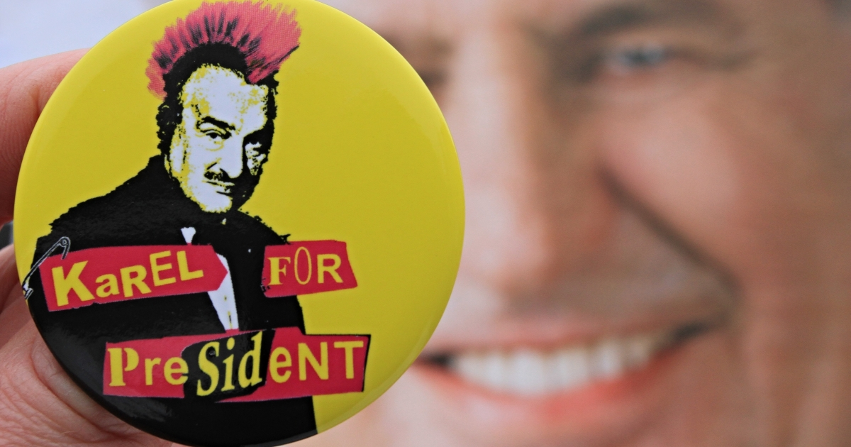 A button depicting Czech presidential candidate Karel Schwarzenberg as a punk with red hair in front of a campaign poster of rival Milos Zeman.</p>