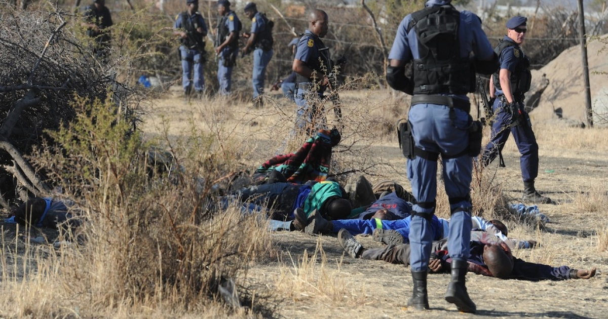 Police surround miners killed during clashes between protesting miners and police near a platinum mine in Marikana on Aug. 16, 2012.</p>