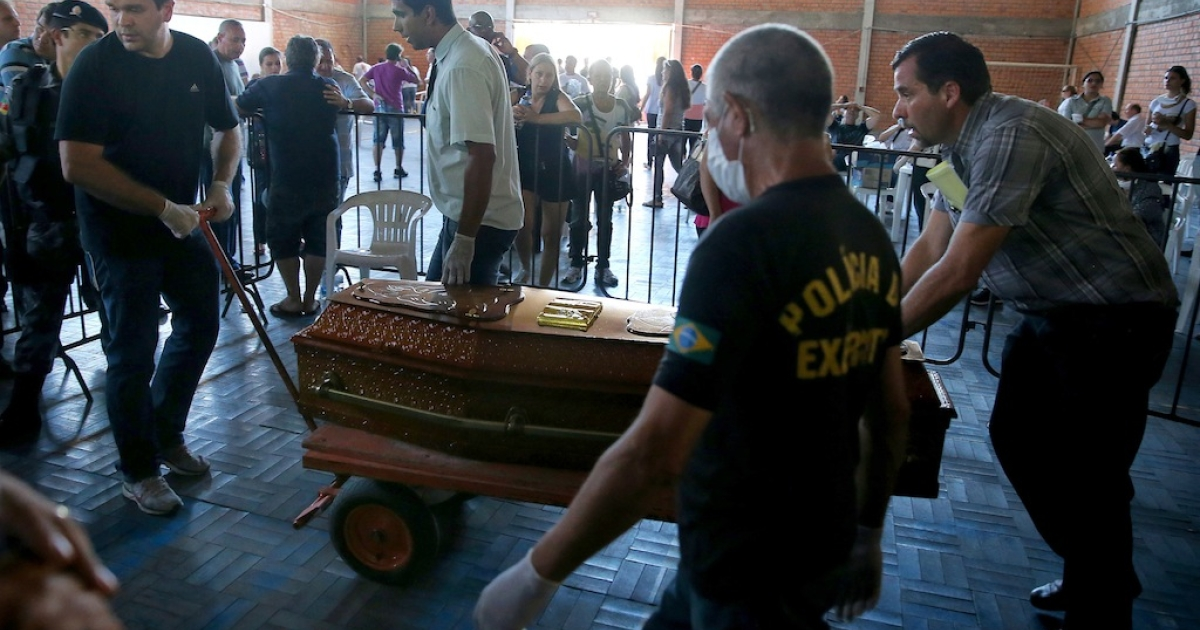 Relatives of a victim killed in the Kiss nightclub blaze carry a coffin at the municipal gymnasium on Jan. 28, 2013 in Santa Maria, Brazil.</p>