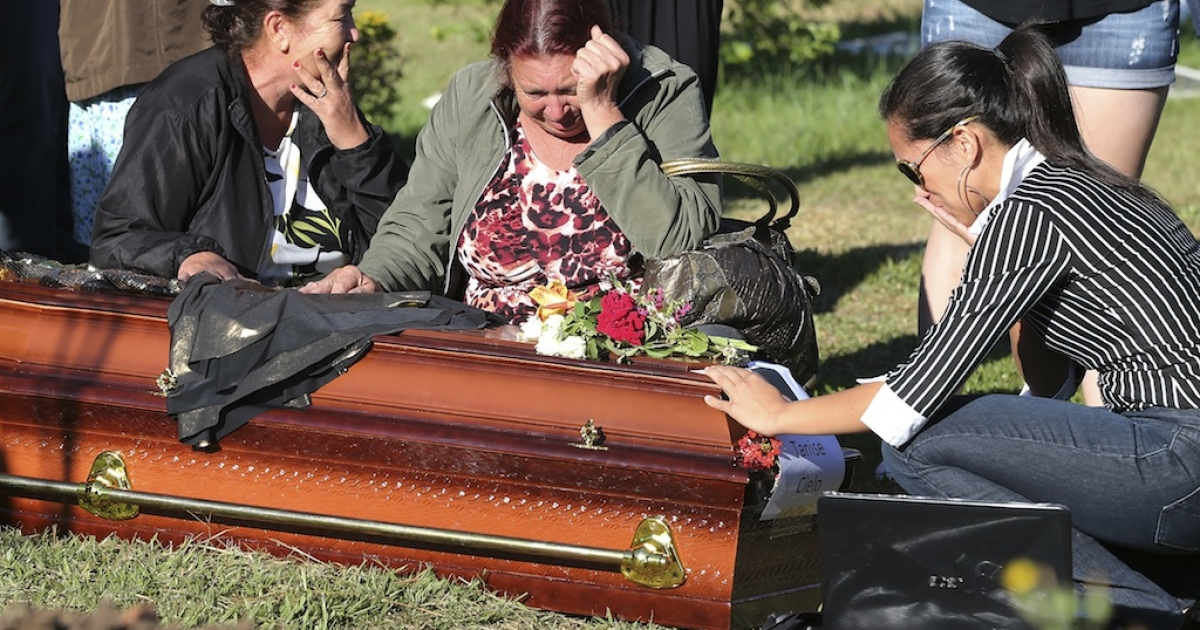 Relatives and friends of Tamise Cielo, one of the victims of the Kiss nightclub fire, gather around her coffin during the funeral at Santa Rita cemetery on Jan. 28, 2013.</p>