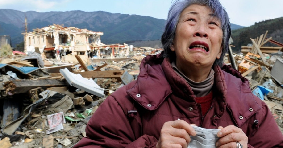An elderly woman cries in front of a destroyed building in the devastated town of Rikuzentakata in Iwate prefecture on March 19, 2011, eight days after a massive 9.0 magnitude earthquake and tsunami hit the northeastern coast of Japan's main island of Honshu.</p>