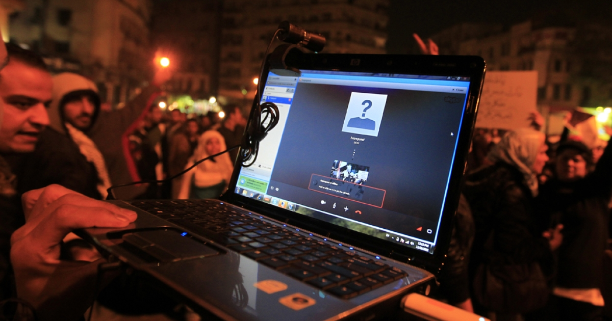 An Egyptian protester streams a demonstration via Skype as people gather in Cairo's Tahrir Square on December 20, 2011. A group of internet activists, privacy advocates and journalists called on Skype to clarify its privacy policy on January 25, 2013.</p>