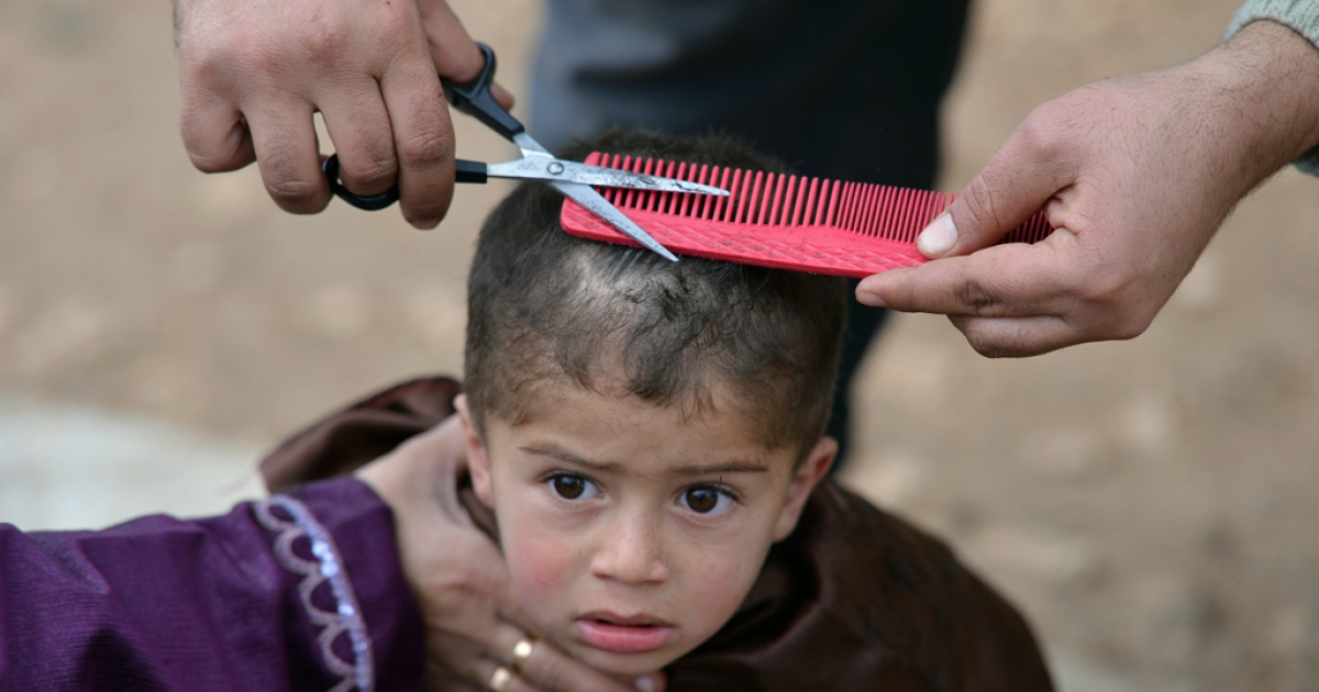 A displaced Syrian boy gets a haircut at a makeshift refugee camp in Atmeh, in the northwestern province of Idlib along the Turkish border, Jan. 31 2012.</p>