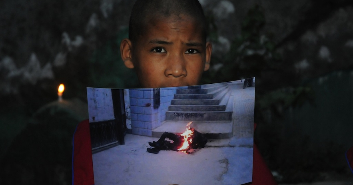 An exiled Tibetan monk holds a picture of 50-year-old, Tamdin Thar, who burned himself to death to protest against the Chinese rule in Tibet during a rally on June 15, 2012. Chinese authorities have gotten increasingly strict with Tibetans, as self-immolations continue.</p>