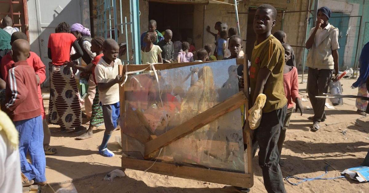 A man an a child carry a mirror as residents plunder stores they say belong to Arabs, Mauritanians and Algerians who they accuse of supporting the Al Qaeda-linked Islamists, on Jan. 29, 2013 in Timbuktu.</p>