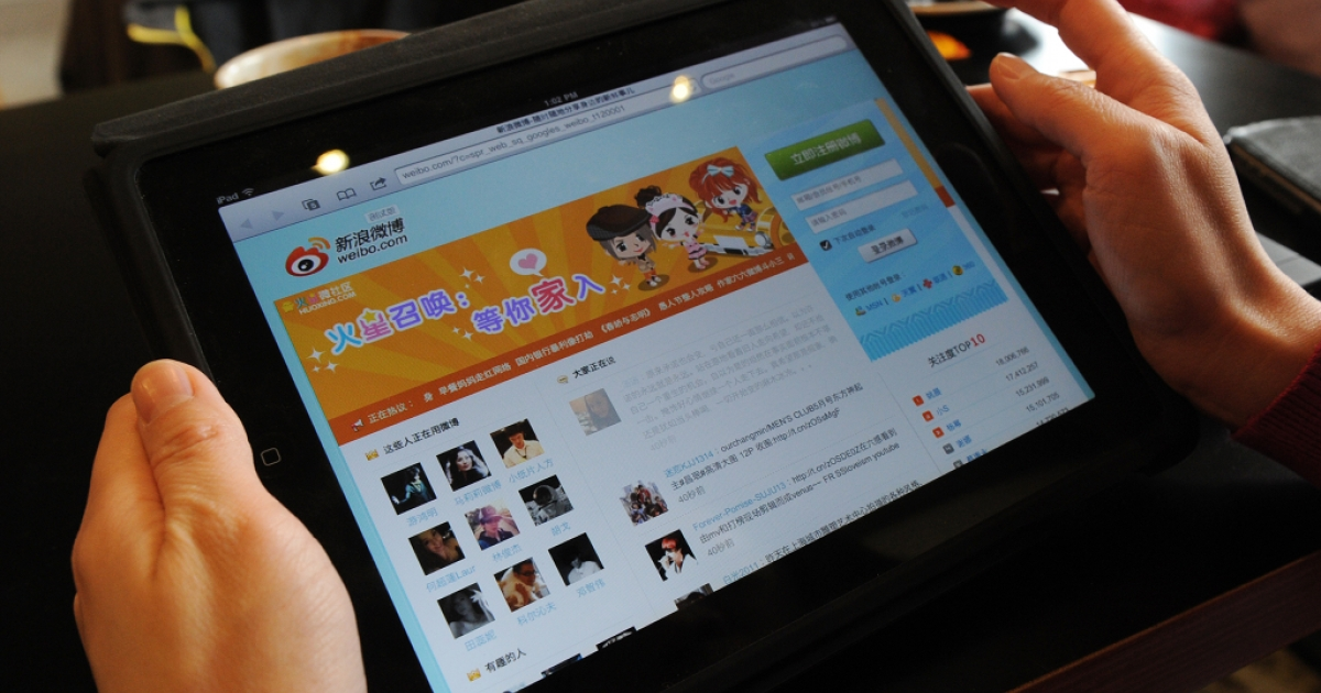 A woman views the Chinese social media website Weibo at a cafe in Beijing on Apr. 2, 2012. In an effort to minimize the influence of dissenting voices on the microblogging site, the Chinese government will employ millions of workers to post pro-party messages.</p>
