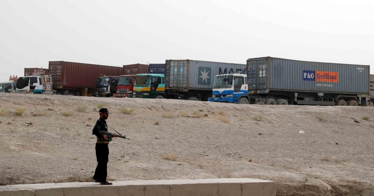 A Pakistani security serviceman stands guard beside container trucks carrying NATO supplies parked at the border town of Chaman on July 27, 2012.</p>
