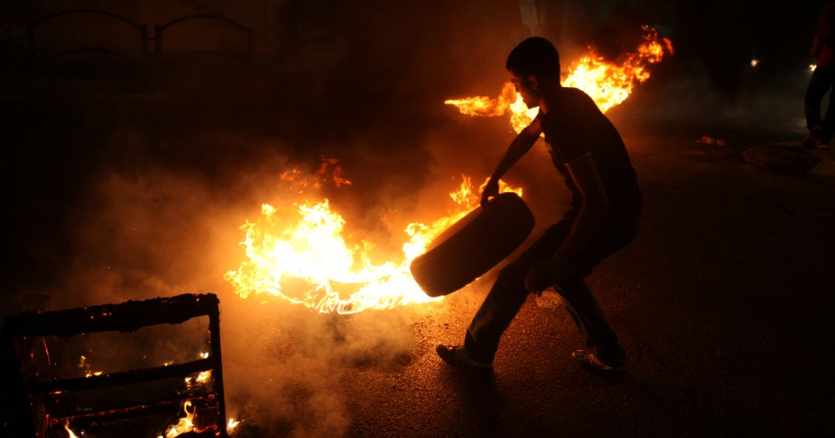 A Palestinian youth burns tires during a protest against the high cost of living at Al-Amari refugee camp near the West Bank city of Ramallah on September 8, 2012.</p>