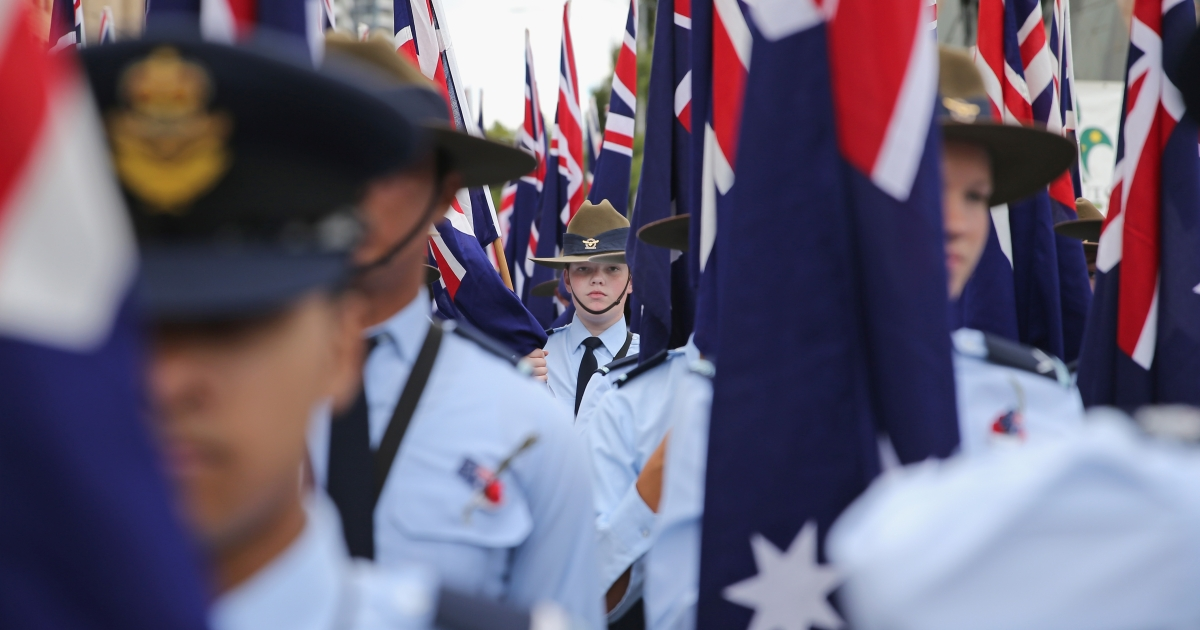 Members of the Australian Air Force Cadets hold Australian flags as they march during the annual Anzac Day march on April 25, 2013 in Melbourne, Australia.</p>